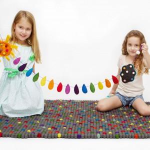 Prostokątny dywan stworzony z małych pomponików o wzorze przypominającym pixele. Doskonała propozycja do pokoju dziewczynek oraz chłopców. Fot. Happy as Larry Design.