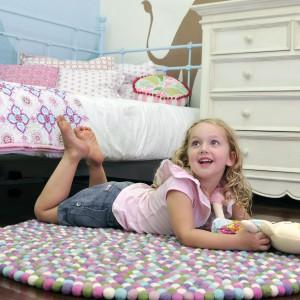 Okrągły dywan Sorbet bazujący na setkach połączonych ze sobą kulek w pastelowych kolorach, podkreśli subtelny charakter pokoju kilkulatki. Fot. Happy as Larry Design.