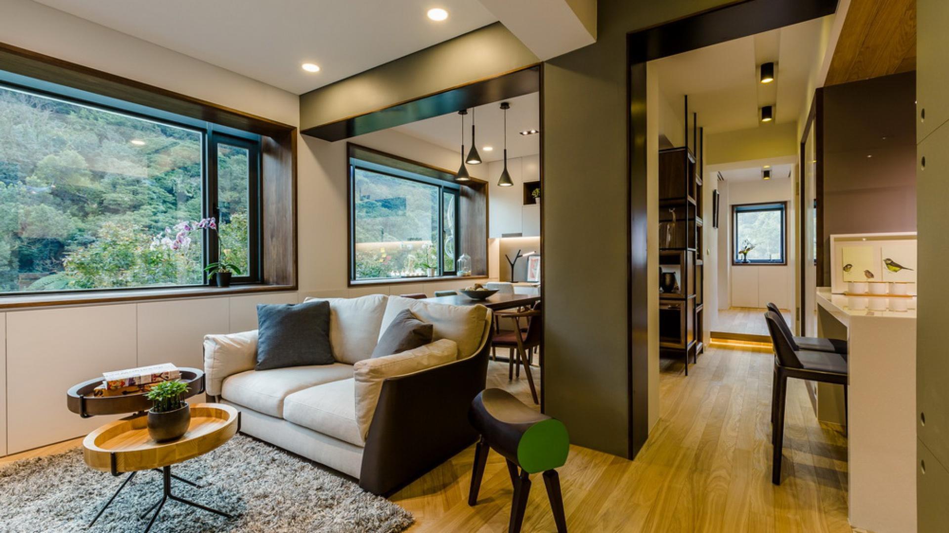 Przestrzeń dzienna obejmuje salon, połączony w jednym rzędzie z jadalnią, która przechodzi płynnie w niewielki gabinet. Po drugiej stronie korytarza urządzono kuchnię. Projekt i zdjęcia: Archlin Studio.