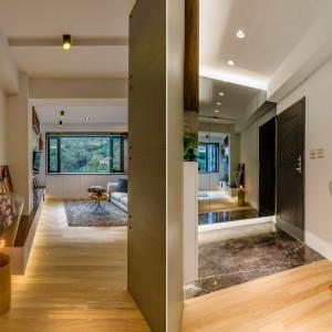Przedpokój wykończono jasnymi barwami - drewniana podłoga i białe ściany z sufitem budują przytulny, gościnny nastrój. Podłogę przy wejściu wykończono posadzką z naturalnego kamienia - praktyczne rozwiązanie, zwłaszcza w deszczowe dni. Projekt i zdjęcia: Archlin Studio.