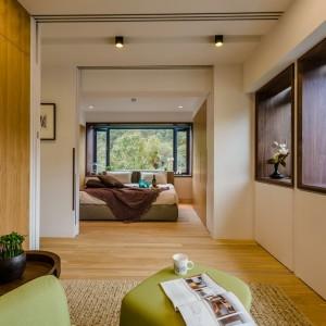 Aby wpuścić do wnętrza światło oraz adekwatnie oprawić malowniczy widok za oknem, wielodzielne okna w metalowych ramach zastąpiono dużymi przeszkleniami w drewnianej oprawie. Projekt i zdjęcia: Archlin Studio.