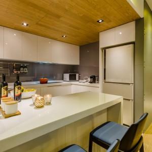 Kuchnię wykończono w modnym połysku. Białe fronty bez uchwytów, szkło na ścianach - wszystko jest połyskujące i nadaje przestrzeni niezwykle lekki charakter. Projekt i zdjęcia: Archlin Studio.