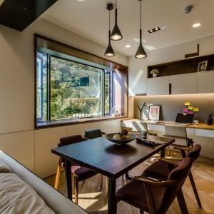 Jadalnię połączono z niewielkim gabinetem, który przyjął formę mebli na jedną ścianę i towarzyszącego im krzesła. Nad stołem jadalnianym zawisły efektowne, dekoracyjne lampy w eleganckich, czarnych oprawach. Projekt i zdjęcia: Archlin Studio.