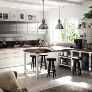 Połączenie metalowych elementów z lakierowanym drewnem idealnie wpisuje się w stylistykę vintage. Klimatyczne dodatki, jak robot kuchenny i radio w stylu retro zdobią kredens i komodę na kółkach w stylu industrialnym. Fot. Scavolini/Diesel Living.
