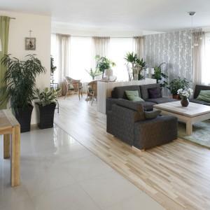 Elementem różnicującym poszczególne pomieszczenia jest podłoga. Salon wyścielono jesionowym parkietem, natomiast jadalnię i kuchnię wykończono praktycznym gresem. Fot. Bartosz Jarosz.