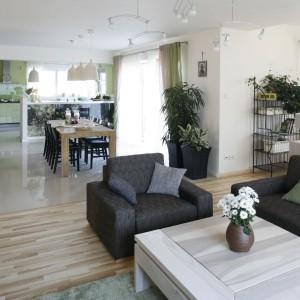 Zarówno w salonie, jak i jadalni pojawiają się zielone akcenty w postaci poduszek dekoracyjnych czy zasłon. Nawiązują one do barwy, dominującej w aranżacji kuchni. Fot. Bartosz Jarosz.