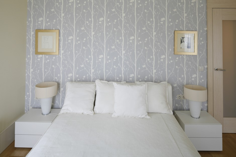 Pastelowa tapeta z białym, roślinnym wzorem dopełnia spokojna aranżację sypialni. Projekt: Małgorzata Borzyszkowska. Fot.Bartosz Jarosz.