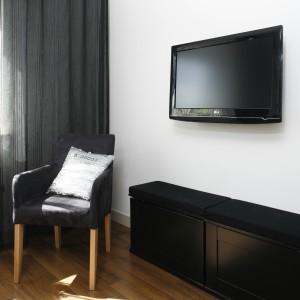 Czarny ekran na tle białej ściany znakomicie komponuje się z całą aranżacją. Efekt dopełnia nowoczesna szafka RTV z czarnymi, lakierowanymi frontami. Projekt: Małgorzata Mazur. Fot. Bartosz Jarosz.