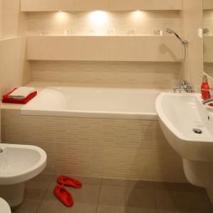 Łazienka o pow. 5,5 m kw wydaje się przestronna dzięki zastosowaniu jasnych, beżowych okładzin. Szczypta czerwieni w postaci dodatków ożywia wnętrze. Projekt: właściciele. Fot. Bartosz Jarosz.