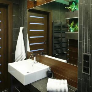 W tej łazience o pow. 5 m kw.  wszytko służy optycznemu powiększeniu przestrzeni. Poziomo ułożone płytki, lustra oraz mozaika, która urozmaica okładziny. Projekt: Marta Kila. Fot. Bartosz Jarosz.