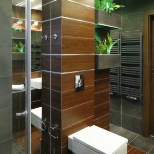 Za pomocą różnych materiałów wyznaczono strefy łazienki: płytki jak drewno ułożone zostały w strefie sanitarnej, a szare imitujące beton - w strefie prysznica. Projekt: Marta Kila. Fot. Bartosz Jarosz.