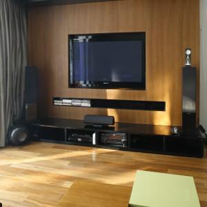 Przestrzeń ściany telewizyjnej pokrywa drewniany fornir, w którym stworzono wnęki na ekran i piloty. Sprzęt DVD ustawiono na nowoczesnej, niskiej szafce, która nadaje elegancji. Projekt: Dąbrówka Potowska. Fot. Batrosz Jarosz.
