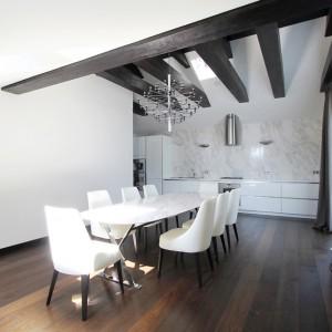 W kuchni i jadalni ścierają się dwa odmienne style. Żyrandol w stylu francuskim i kamienny blat stołu nawiązują do klasycznej stylistyki, podczas gdy stalowe, skrzyżowane nogi mebla i minimalistyczna zabudowa w kuchni wpisują się w nowoczesne wzornictwo. Projekt: Ramūnas Manikas, Valdas Kontrimas. Fot. Ramūnas Manikas.