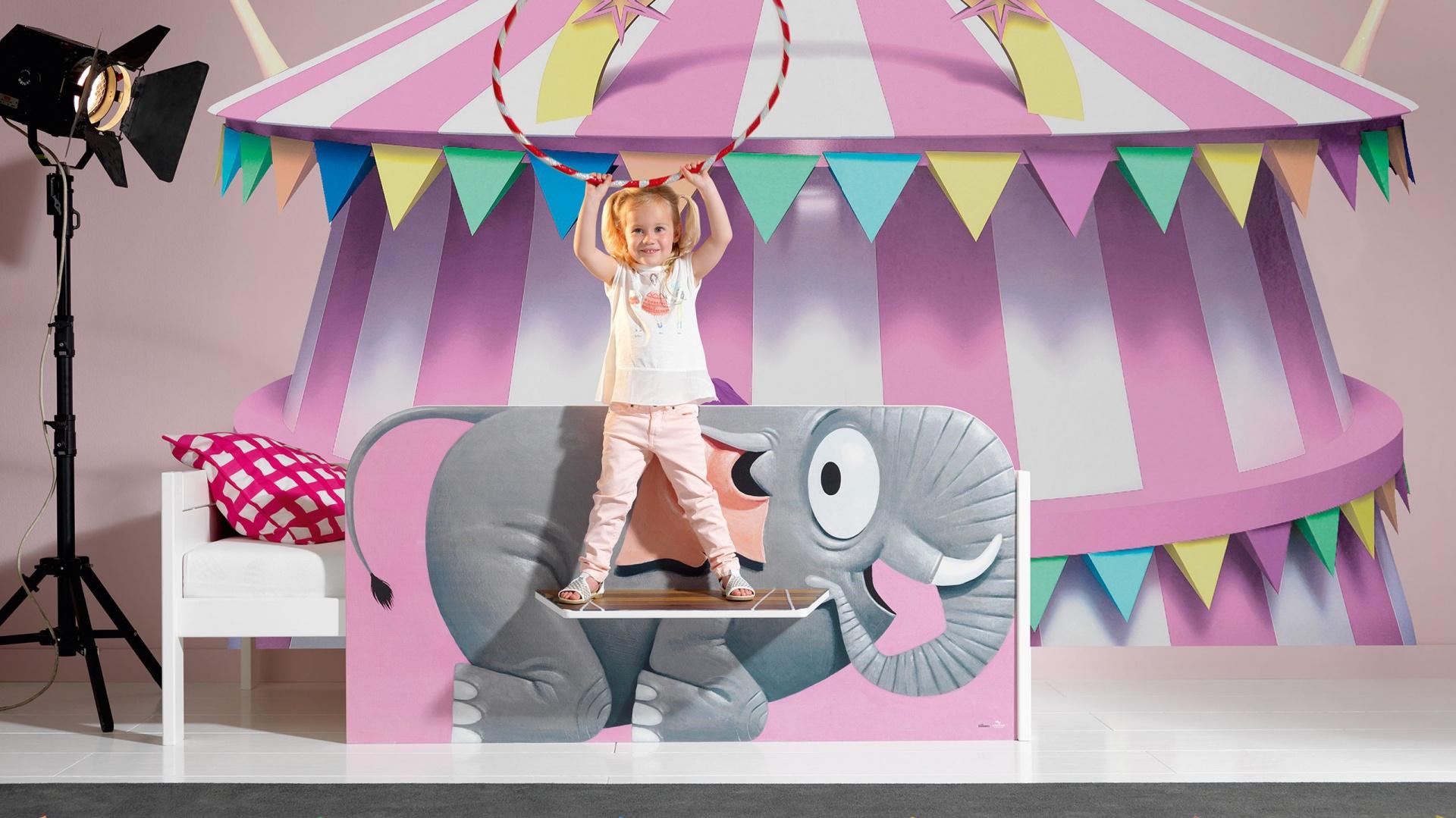 Pokój dziecka może być prawdziwą areną cyrkową. Atmosferę widowiska wprowadzi do wnętrza fototapeta z motywem namiotu cyrkowego oraz oryginalne łóżko. Klimat zbuduje też oświetlenie w postaci lampy-reflektora. Fot. Cuckooland.