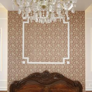 Na ścianie za łóżkiem umieszczono dekoracyjną tapetę. Dodatkowo powtórzono motyw po obu stronach łóżka. Tapeta w połączeniu z ramą wykonaną z ozdobnej sztukaterii tworzy ciekawą dekorację. Fot. Bartosz Jarosz.