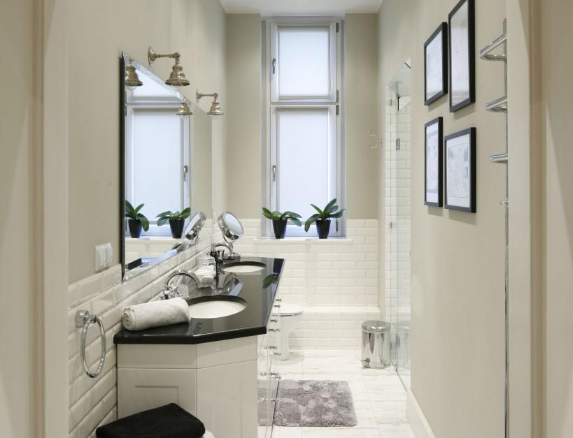 Bardzo wąska łazienka została wykończona białymi kaflami. Ułożone poziomo wizualnie poszerzają wnętrze. Dodatkowo biel i połyskujące powierzchnia rozjaśniają łazienkę. Projekt: Iwona Kurkowska. Fot. Bartosz Jarosz.