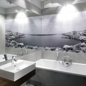 Ścianę nad wanną zdobi fototapeta, a zabezpiecza szkło. Wakacyjny widok na wybrzeże Toskanii wprowadza do łazienki wyjątkowy klimat. Projekt: Lucyna Kołodziejska. Fot. Bartosz Jarosz.
