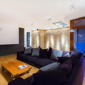 Rolę stolika kawowego pełni drewniana paleta na kółkach. Wprowadza ona do wnętrza delikatnie loftowy klimat, korespondując z cegłą na ścianie. Fot. Marek Białokoz.