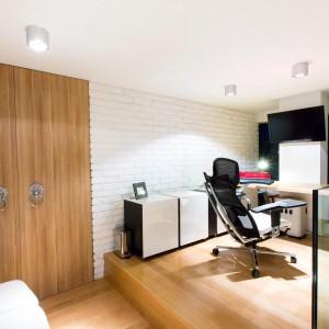 Funkcjonalny gabinet wyposażono w podest, na którym usytuowano kącik do pracy oraz niższą część pomieszczenia z kanapą, na której można odpocząć. Ścianę wykończono pomalowaną na biało cegłą. Fot. Marek Białokoz.