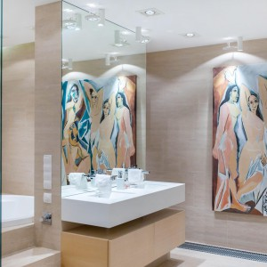 W łazience, zdominowanej przez beże, akcentem ożywiającym przestrzeń jest kolorowy obraz. Duże lustro nad umywalką duplikuje wizualnie malunek i dodatkowo wprowadza kolor do wnętrza. Fot. Marek Białokoz.