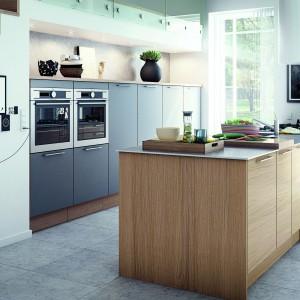 Kuchnia, w której dominują różne odcienie zimnej szarości została ocieplona dużą wyspą kuchenną, w całości wykończoną w drewnianym dekorze. Połączenie ciepłego odcieniu drewna z zimnymi, satynowymi, szarymi powierzchniami nadaje przestrzeni elegancki charakter. Fot. HTH, model Eg.