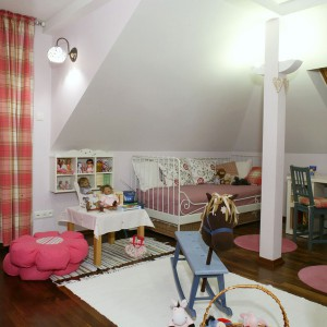 Po przeciwnej stronie pomieszczenia ustawiono piękne, kute łóżko z wiklinowym koszem na pościel. Projekt: Lucyna Stefaniak. Fot. Monika Filipiuk-Obałek.