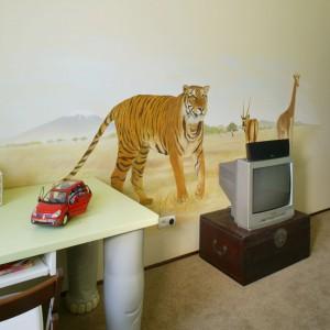 Przeniesiony z Afryki malunek to element aranżacji ściany telewizyjnej w pokoju dziecka. Egzotyczne zwierzęta pilnują, by pilot nie dostał się w niepowołane ręce. Projekt: Beata Kozieradzka. Fot. Bartosz Jarosz.