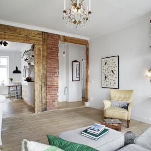 W salonie wzrok przyciąga oryginalna ściana. Obok powierzchni pomalowanych na biało, część ściany, okalającej drzwi, pokrywa drewno i naturalna cegła. Wprowadzają one ciekawy efekt wizualny do wnętrza salonu. Fot. Stadshem.se/Janne Olander.