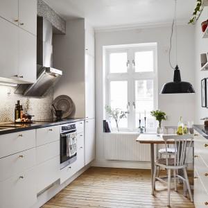 Kuchnię urządzono w oparciu o układ dwurzędowy. Funkcjonalne umeblowanie pozwoliło wpasować w przestrzeń pomiędzy meblami a oknem, niewielki stół. Fot. Stadshem.se/Janne Olander.