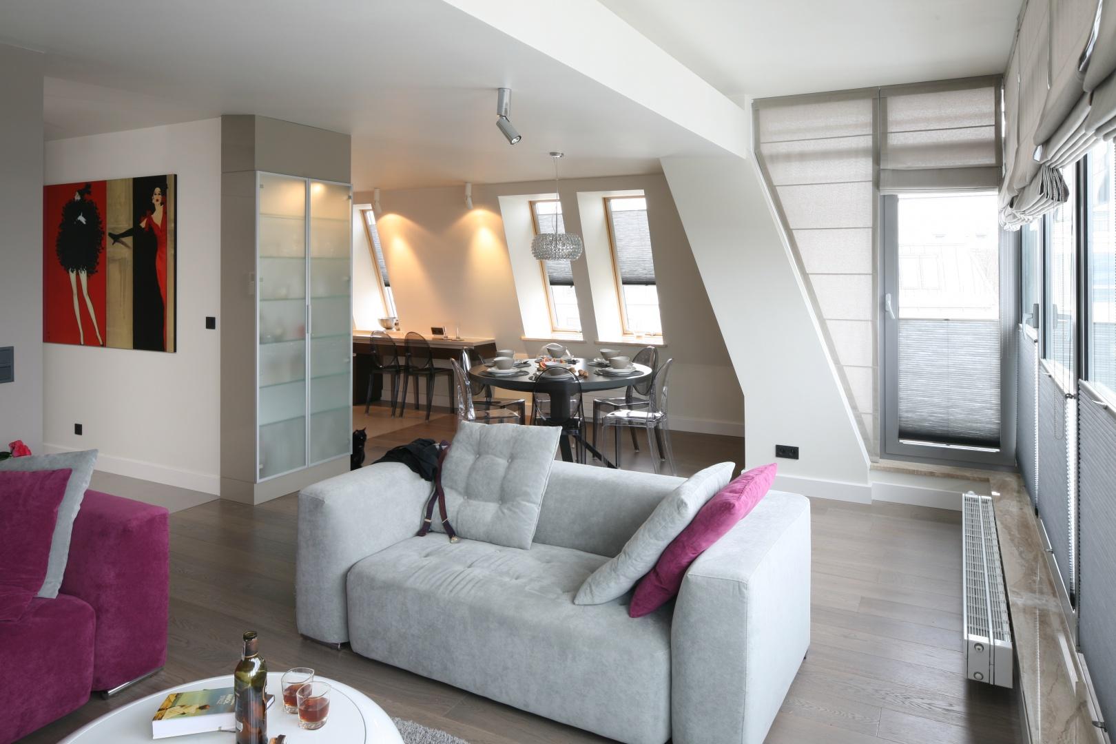 Liczne przeszklenie mieszkania na poddaszu pięknie otwierają przestrzeń na to, co na zewnątrz. Aby uchronić gospodarzy przed nadmiarem słońca, okna wyposażono w transparentne rolety. Projekt: Małgorzata Borzyszkowska. Fot. Bartosz Jarosz.
