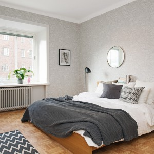 Sypialnia urządzona w jasnych odcieniach szarości doskonale komponuje się z drewnianą podłogą. Fot. Alvhem Mäkler.