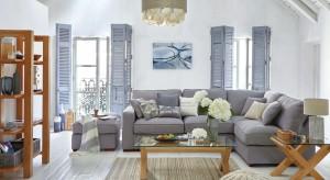 Chociaż salon urządzony jest w bieli i szarości, to jednak zachwyca skandynawskim, a zarazem ciepłym wyglądem. Duża w tym zasługa prostych, drewnianych mebli.