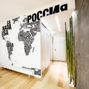 Ściana w salonie została udekorowana mapą świata, ułożoną z nazw poszczególnych państw, zapisanych różnymi alfabetami. Projekt i zdjęcia: Brain Factory.
