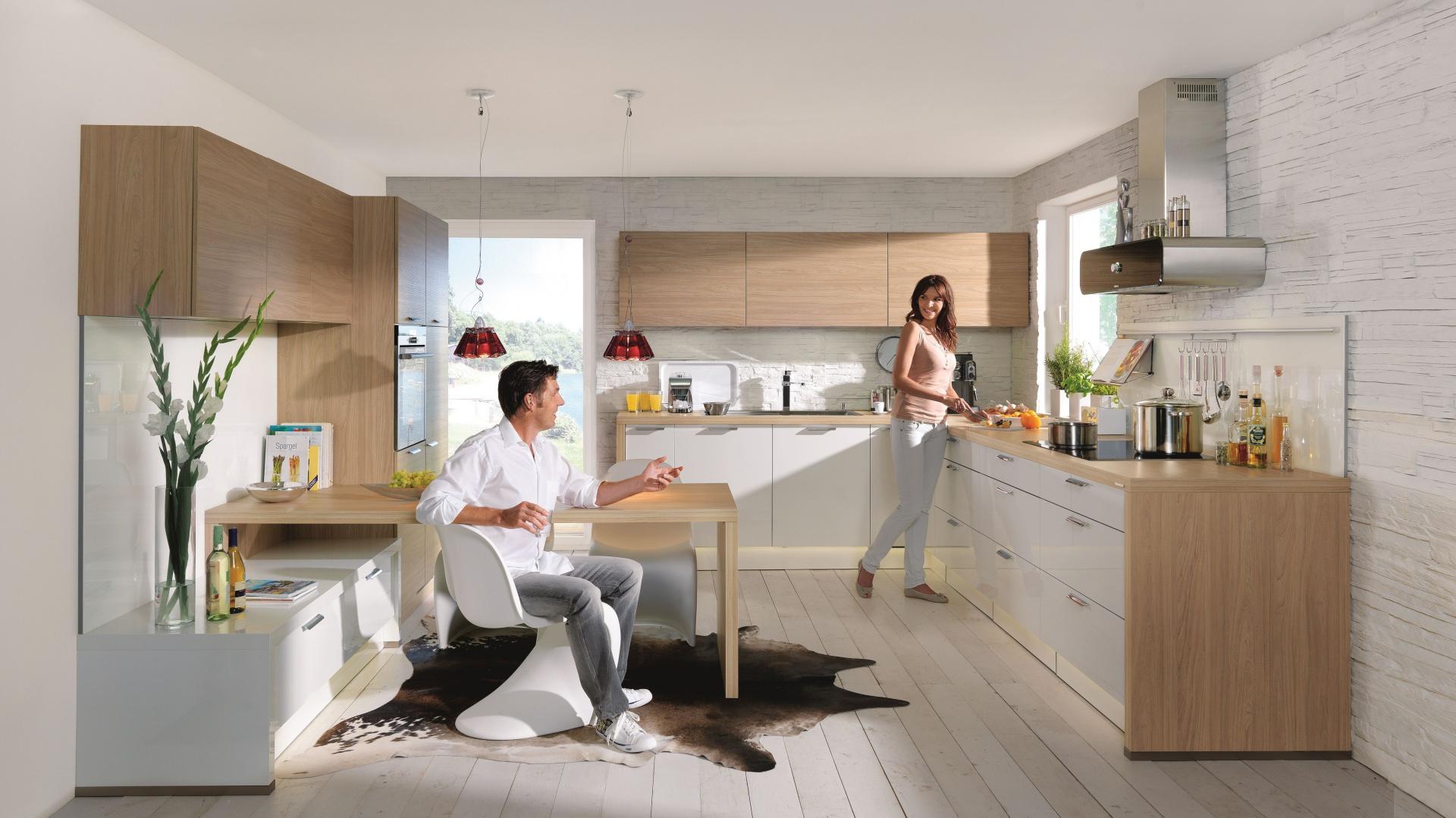 Przykład pięknej, modnej kuchni w bieli i drewnie. Połyskujące białe fronty zestawiono z kolorem jasnego drewna (Provence elm). Fot. Nolte Kuechen, meble Manhattan 494/Lux 367.