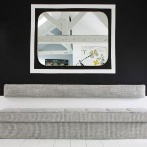 Jedną ze ścian w salonie pomalowano farbą w mocnym, czarnym kolorze. Na jej tle wyeksponowano lustro w dekoracyjnej ramie, która dodatkowo oddziela element od czarnego tła. Po obu stronach lustra zawisły designerskie lampy o fantazyjnej formie. Projekt: Sarah Lavoine. Fot. Francis Amiand.