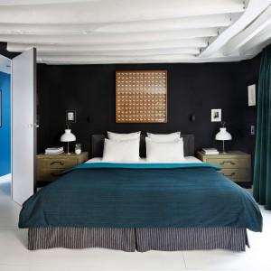 Ściany w sypialni pomalowano czarną farbą, kontrastującą efektownie z białym sufitem. Uniwersalny duet i bieli został wzbogacony kolorami ciemnej zieleni w postaci tekstyliów w oknach i na łóżku. Projekt: Sarah Lavoine. Fot. Francis Amiand.