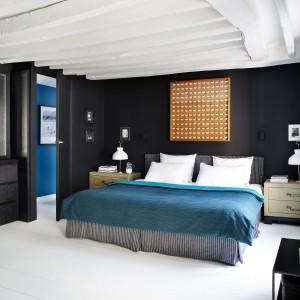 Na tle czarnej ściany stoją wyeksponowane poprzez kontrast kolorów, jasnobrązowe szafki nocne, na których z kolei postawiono - również kontrastujące - białe lampki nocne. Nad łóżkiem zawisło interesujące wizualnie dzieło sztuki japońskiego designera, którego motywem przewodnim są papierowe motyle. Projekt: Sarah Lavoine. Fot. Francis Amiand.