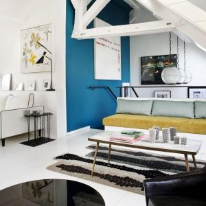 Wyeksponowane belki stropowe stanowią pełnoprawny element dekoracyjny salonu oraz podstawę do zawieszenia efektownych lamp, górujących nad schodami. Projekt: Sarah Lavoine. Fot. Francis Amiand.