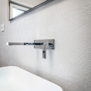 Ściany w łazienkach również mają interesujące wykończenie. W mniejszej - zwieńczono je teksturą w postaci fali, tutaj z kolei wykończono wzorzystymi płytkami z pięknym, trójwymiarowym wzorem. Projekt i zdjęcia: Marco Marotto, Paola Oliva, Brain Factory.