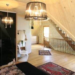 Przestrzeń przy schodach zabezpieczono drewnianą balustradą z ręcznie zdobionymi tralkami. Projekt: Agnieszka Burzykowska-Walkosz. Fot. Bartosz Jarosz.