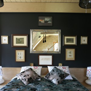 Czarna ściana za łóżkiem to znakomite tło do ekspozycji obrazów czy zdjęć. W ten sposób powstała efektowna wystawa, której centralne miejsce zajmuje lustro w połyskującej ramie. Projekt: Agnieszka Burzykowska-Walkosz. Fot. Bartosz Jarosz.