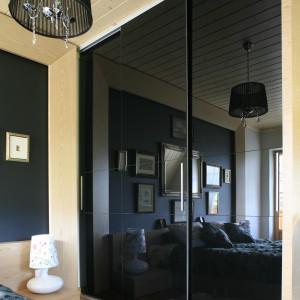 Lakierowane, czarne fronty szafy podkreślają nowoczesny charakter sypialni w Zakopanem. Projekt: Agnieszka Burzykowska-Walkosz. Fot. Bartosz Jarosz.