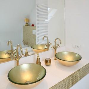 Łazienka urządzona jest z przewagą bieli, dla której złota mozaika stanowi efektowny dodatek, wykończono nią także rant blatu podumywalkowego. Projekt: Piotr Stanisz. Fot. Bartosz Jarosz.