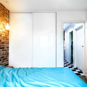 W sypialni wygospodarowano miejsce na pojemną garderobę, schowaną za przesuwnymi drzwiami. Gładki fronty i biel sprawiły, że drzwi zdają się znikać w ścianie. Projekt: COCO Pracownia projektowania wnętrz. Fot. Łukasz Markowicz.