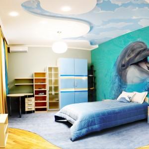 Połączenie niebieskiego ze spokojną żółcią zaowocowało piękną aranżacją. Jej głównym bohaterem jest sympatyczny delfin na efektownej fototapecie marki Minka. Fot. Minka.