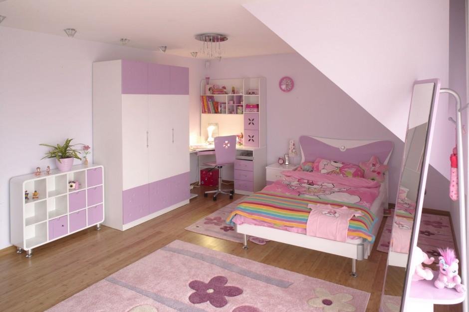 Kwiatowy motyw pojawia się nie tylko na ścianie, ale także na miękkich dywanach. Większy ułożony jest na środku pomieszczenia, natomiast mniejszy – bezpośrednio przy łóżku oraz biurku. Projekt: Kinga Śliwa. Fot. Bartosz Jarosz.