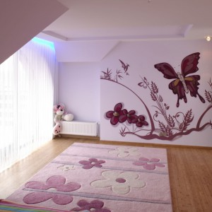 Rysunek przedstawiający kwiaty i motyle rozwesela wnętrze, zdobiąc całą płaszczyznę ściany przy drzwiach. Dzięki dużym oknom dekoracja jest znakomicie oświetlona. Projekt: Kinga Śliwa. Fot. Bartosz Jarosz.