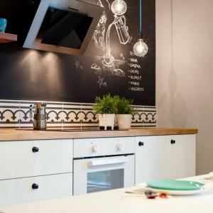 Ścianę nad blatem w kuchni pomalowano praktyczną farbą tablicową, pozwalającą na zapisywanie notatek i zostawianie wiadomości domownikom. Projekt: Raca Architekci. Fot. Adam Ościłowski.
