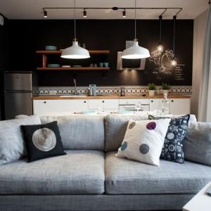 Umowną granicę pomiędzy salonem, a kuchnią wyznacza stół jadalniany i górujące nad nim dwie wiszące lampy, wyeksponowane optycznie poprzez jasną barwę opraw, kontrastujących z czarną ścianą. Projekt: Raca Architekci. Fot. Adam Ościłowski.