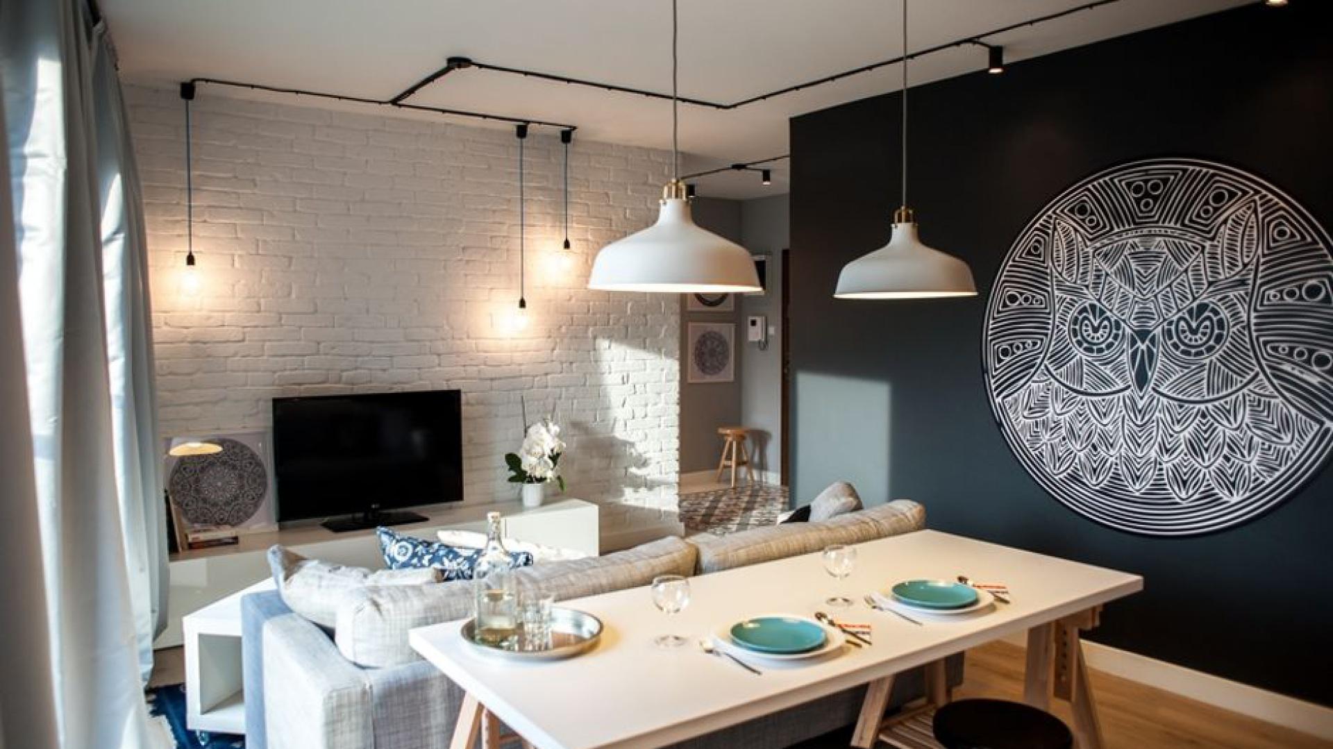 Najbardziej charakterystycznym elementem dekoracyjnym we wnętrzu jest mandala z motywem sowy na czarnej ścianie. Jest to wielkoformatowy nadruk na płycie PVC. Projekt: Raca Architekci. Fot. Adam Ościłowski.